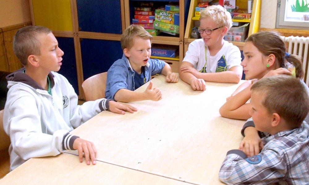 Kinder sitzen am Tisch und diskutieren: Das Deutsche Kinderhilfswerk setzt sich für Kinder- und Jugendbeteiligung ein.