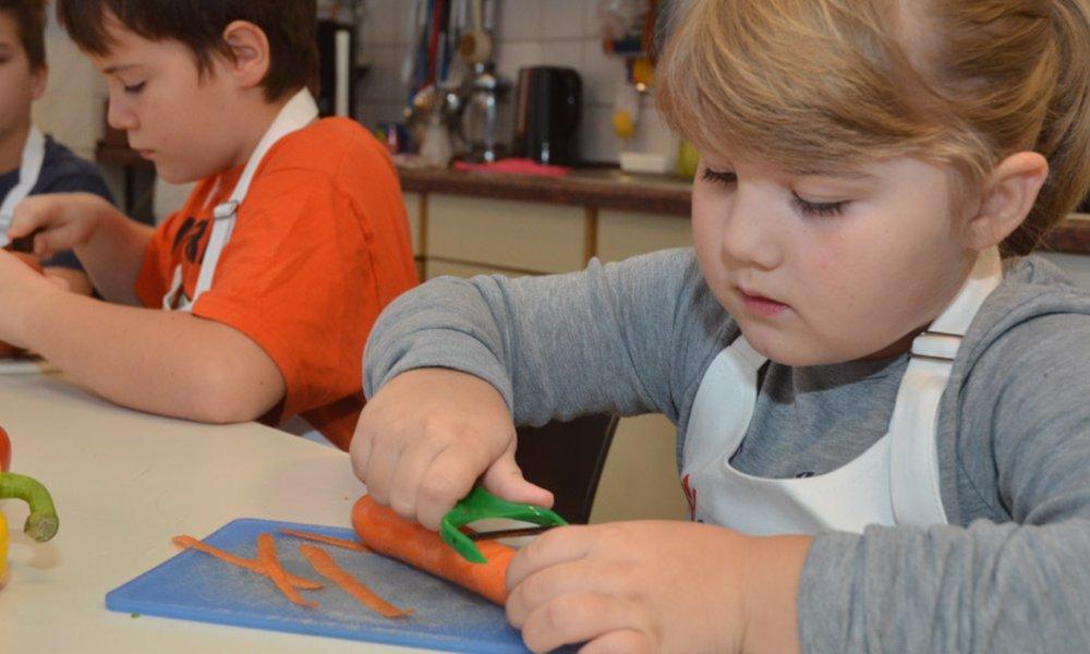 Wir fördern Projekte, in denen Kinder aus schwierigen Verhältnissen lernen, mit einfachen Mitteln zu kochen und so das Essverhalten ihrer Familien zu beeinflussen.
